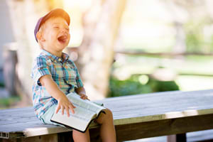 Boy laughing when understand something written in a book